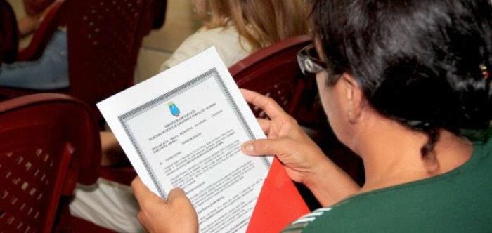 Beneficiária confere documentação da moradia que recebeu