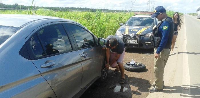 Motorista conserta um dos vários carros com pneus furados nos buracos da BR-135