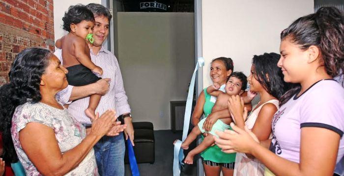 Evangelista carrega um dos meninos, ao visitar a casa