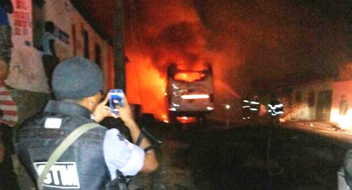 ônibus em chamas e policial filmando a cena; o prejuízos é das empresas (imagem ilustrativa)