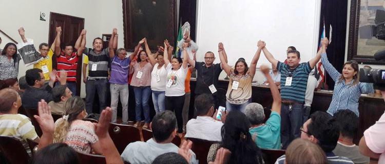 Líderes sindicais levantam as mãos aprovando protesto, sob aplausos da categoria