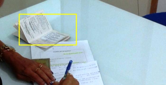 Um dos contratados assina os documentos com a carteira aberta, sob orientação do ISEC
