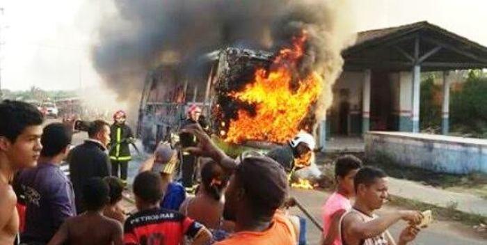 Moradores observam o ônibus queimado; situação ainda fora de controle, apesar das garantias de Flávio Dino